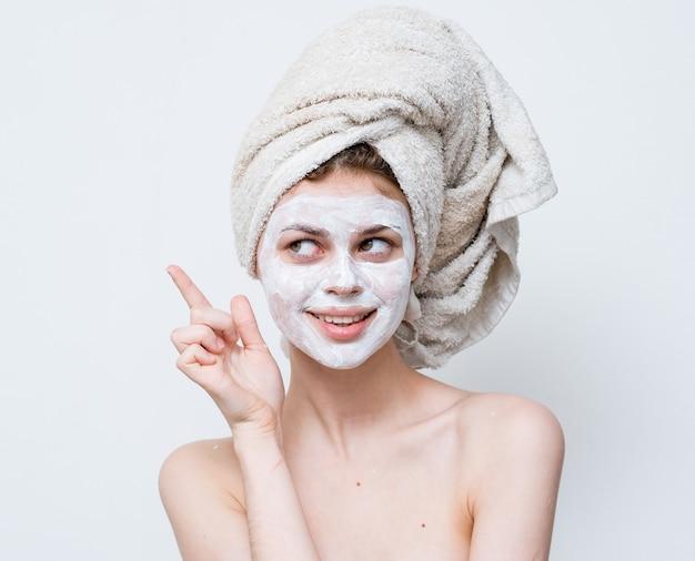 Donna con asciugamano crema viso spalle nude sulla testa.