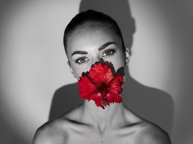 Donna con le spalle nude che tiene in bocca un fiore rosso foto in bianco e nero