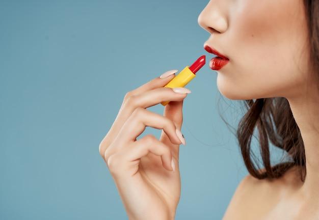 Donna con le spalle nude cosmetici rossetto sfondo blu. foto di alta qualità