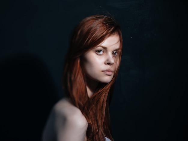 Donna con i capelli rossi delle spalle nude che posano fondo isolato