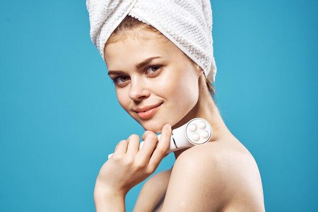 Donna con le spalle nude con un asciugamano sulla testa massaggiatore facciale cura