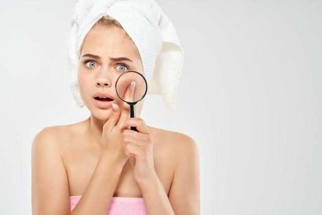 Donna con le spalle nude con gli asciugamani che parlano con la lente d'ingrandimento per problemi di pelle vicino al viso