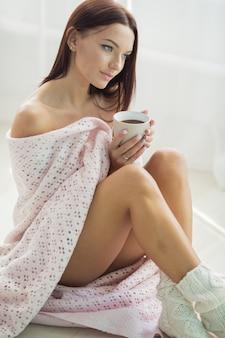 Donna con bellissime spalle nude avvolte in un caldo plaid rosa e calze a maglia a piedi nudi