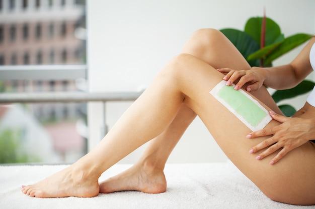La donna con una bella pelle in piedi applica del nastro cerato sulla gamba per rimuovere i peli