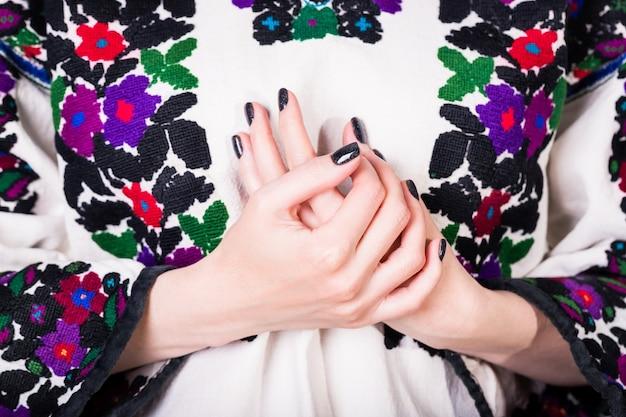 Donna con manicure nera in una vecchia camicia ricamata ucraina