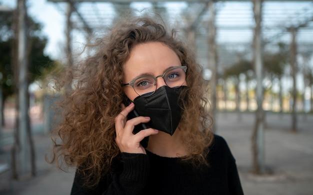 Donna con maschera nera, parlando al telefono in strada
