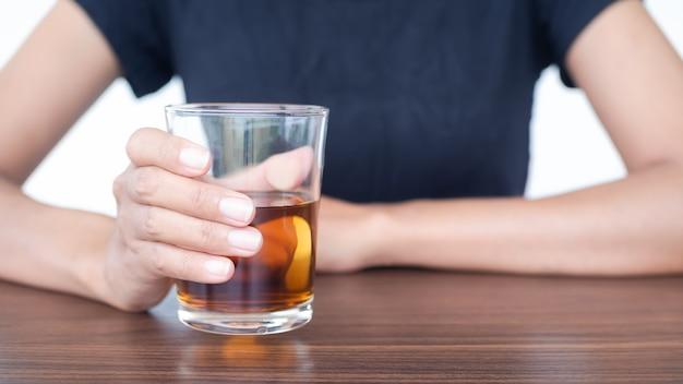 Donna con t-shirt nera che tiene whisky o alcol in vetro su tavolo di legno. abuso di sostanze, sostanza che crea dipendenza, sostanza che crea assuefazione, droga pericolosa per la velocità. persone con problemi di vita.