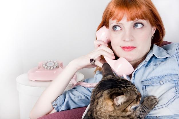 Donna con gli occhi azzurri che parla su un telefono vintage e il suo gatto