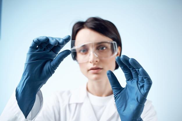 La donna con i guanti blu prova la diagnostica dell'analisi della ricerca