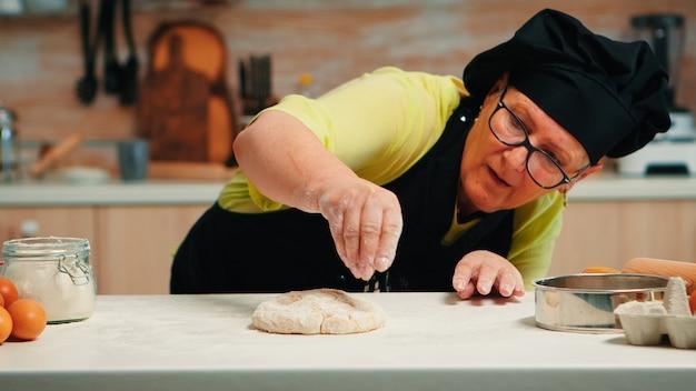 Donna con bonete e grembiule da cucina è occupata con la preparazione dell'impasto. fornaio anziano in pensione con grembiule, spolverata uniforme da cucina, setacciatura, spalmatura di farina con pizza e pane fatti in casa da cuocere a mano.