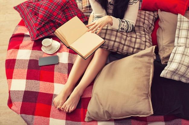 Donna con libro telefono e caffè su plaid natale plaid gambe da vicino