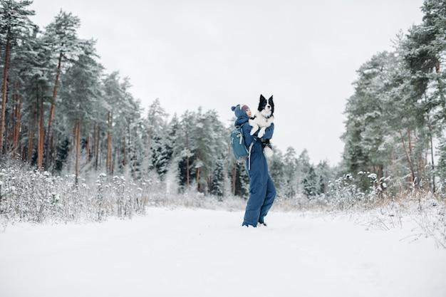 Donna con un cane border collie nella foresta innevata