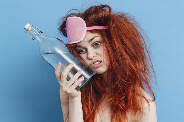 Donna con una bottiglia di alcool dopo una festa, postumi di una sbornia, alcolismo