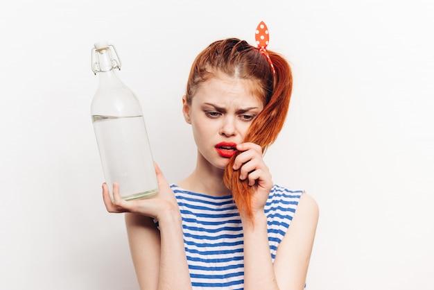 Donna con una bottiglia di alcool nelle sue mani