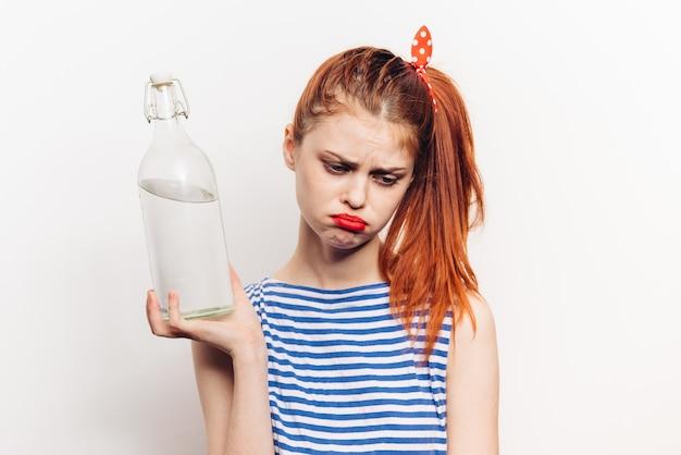 Donna con una bottiglia di alcol nelle sue mani
