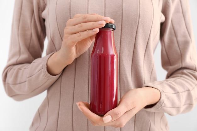 Donna con una bottiglia di frullato sano su superficie bianca, primo piano