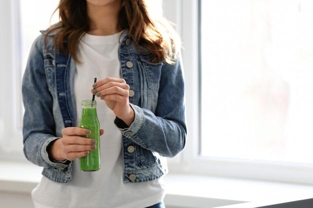 Donna con una bottiglia di gustoso frullato al chiuso