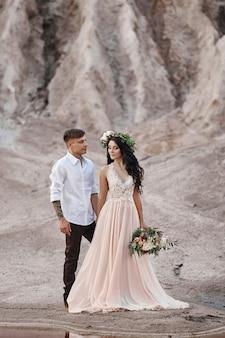 Donna con un mazzo di fiori tra le braccia degli uomini. gli sposi con le montagne sullo sfondo, servizio fotografico di matrimonio nella natura