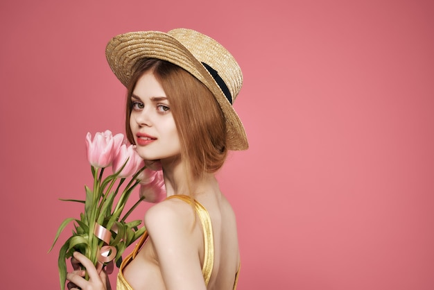 Donna con bouquet di fiori glamour attraente look regalo sfondo rosa. foto di alta qualità