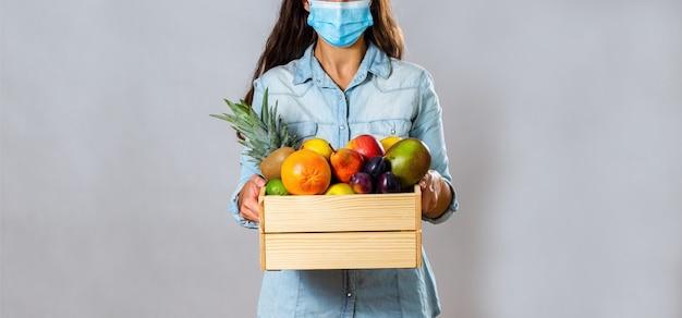 Donna con scatola piena di frutta fresca proteggendo con maschera facciale