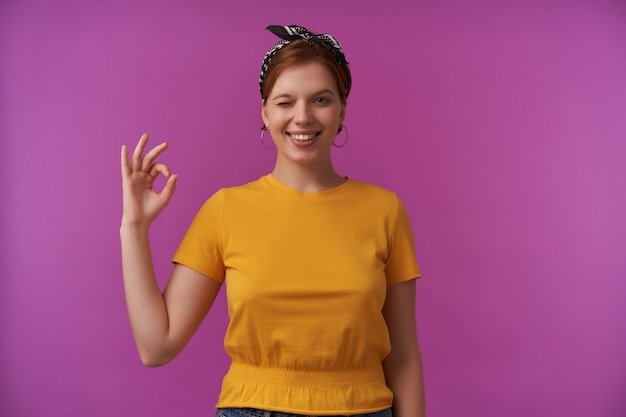 Donna con i capelli castani e trucco naturale che indossa giallo alla moda - maglietta e bandana nera emozione allegro lieto occhiolino okay dita in posa isolato sul muro viola