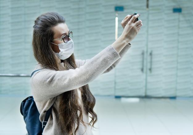 Donna con capelli castani che indossa maschera medica per il viso a causa dell'inquinamento atmosferico o dell'epidemia di virus in città.