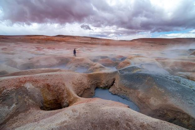 Donna con una macchina fotografica che cammina attraverso alcune fosse di fango
