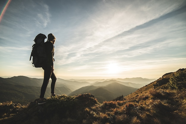 La donna con uno zaino da campeggio in piedi su una roccia con un pittoresco tramonto