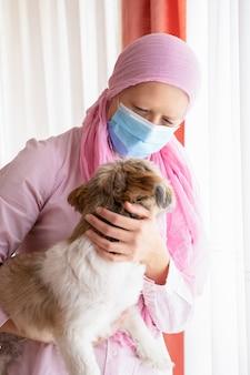 Donna con cancro, velo rosa e maschera che abbraccia il suo animale domestico