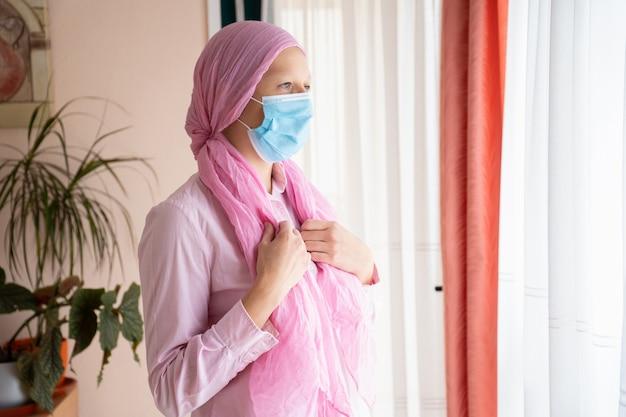 Donna con cancro, velo rosa e maschera guardando fuori dalla finestra