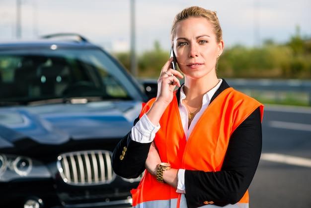 Donna con la ripartizione dell'automobile che chiama la società di rimorchio