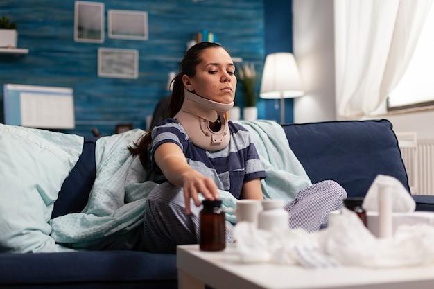 Donna con collare cervicale seduta sul divano che soffre di dolore alla colonna vertebrale. giovane persona caucasica con lesioni fisiche che assume farmaci antidolorifici dopo un incidente alla schiena, con disagio