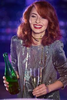 Donna con flute di champagne e bottiglia