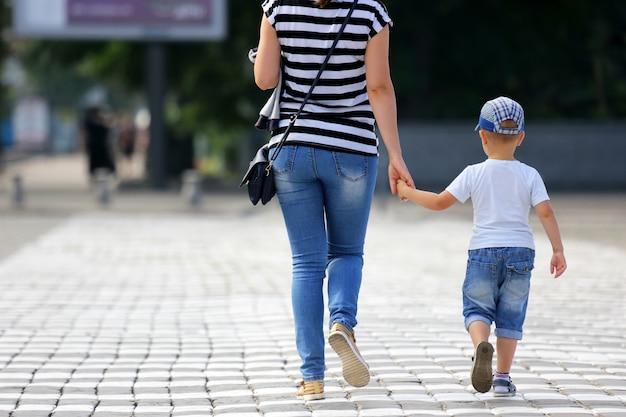 Una donna con un bambino attraversa le strisce pedonali