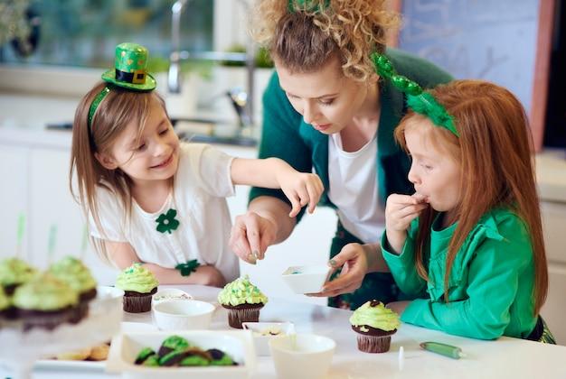 Donna con bambini che decorano i cupcakes