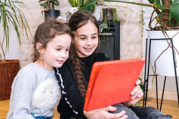 Donna con bambini seduti a casa e in possesso di videocall. famiglia che utilizza smartphone per videochiamata con amici o familiari. le persone comunicano tramite videocamera dall'aspetto video e agitando le mani di saluto