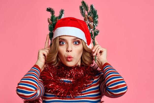 Donna con i rami di un albero di natale nelle mani tinsel rosso e festivo cappello rosa spazio vista ritagliata.