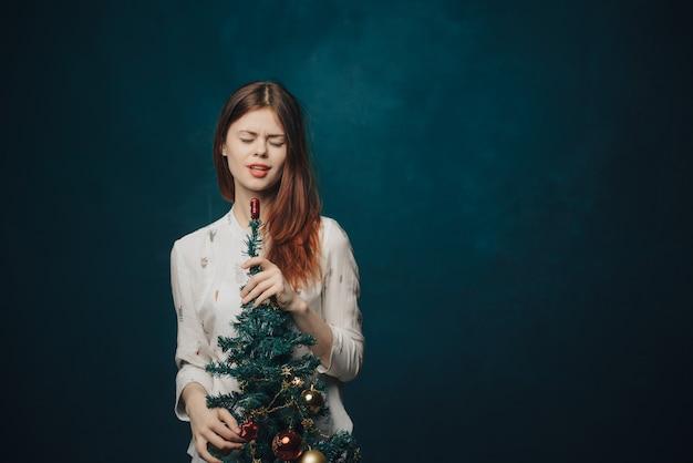 Donna con un albero di natale in mano su uno sfondo blu e palline rotonde giocattoli capodanno od