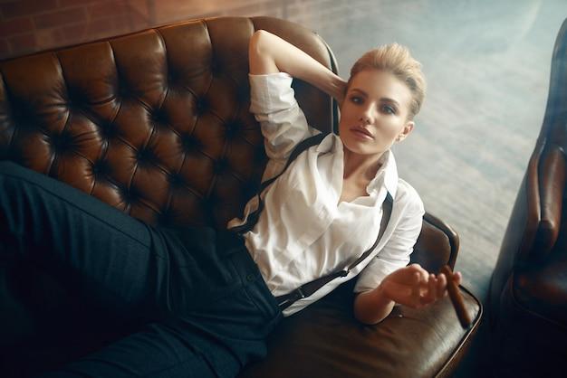 Donna con sigaro sdraiato sul divano