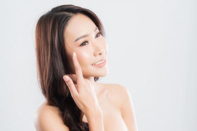 Donna con pelle fresca e pulita, capelli lisci, che propone un prodotto.