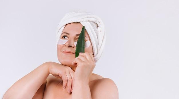 Una donna con la pelle pulita e un asciugamano sulla testa con in mano una foglia di aloe vera. concetto di cura della pelle sana su sfondo bianco con spazio laterale. foto di alta qualità
