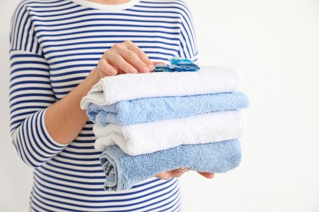 Donna con asciugamani puliti e detersivo su bianco, primo piano