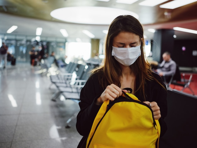 Donna con gli occhi chiusi in maschera medica in attesa dello zaino giallo dell'aeroporto