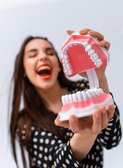 Donna con gli occhi chiusi e la bocca aperta. la tenuta della giovane ragazza ha aperto la mascella educativa del dentista vicino al fronte. concetto dentale. emozioni divertenti.