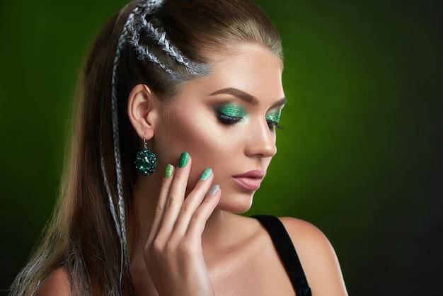 Donna con la sensualità degli occhi chiusi in posa, toccando viso e collo a mano. bella ragazza castana con le sopracciglia marroni, ciglia lunghe, trucco brillante verde alla moda e manicure. concetto di cosmetici.