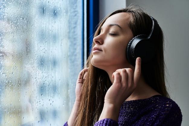 La donna con gli occhi chiusi in cuffia senza fili gode e ascolta musica rilassante rilassante calmante vicino a una finestra con gocce di pioggia durante il tempo piovoso di autunno