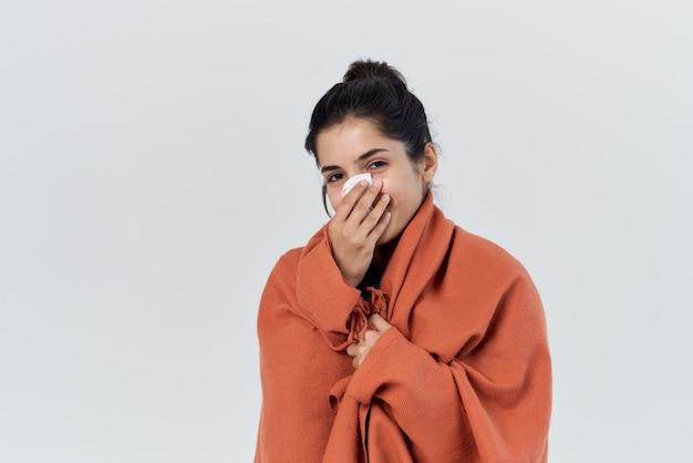 La donna con il raffreddore si è coperta con una coperta per il trattamento dei problemi di salute