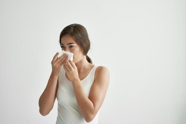 Donna con il raffreddore in una maglietta bianca febbre problemi di salute medicina