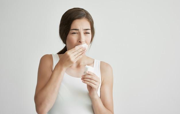 La donna con il raffreddore si asciuga il viso con un fazzoletto emicrania