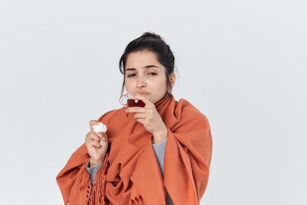 Donna con un raffreddore con medicine in mano si è coperta con una coperta problemi di salute. foto di alta qualità